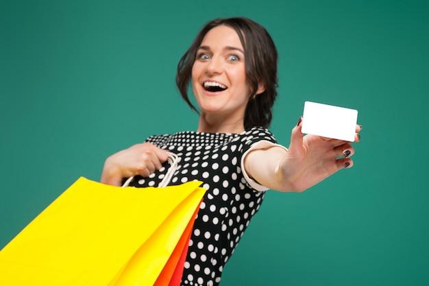 Imagem de mulher bonita em roupas salpicadas de pé com compras e fraque nas mãos Foto Premium