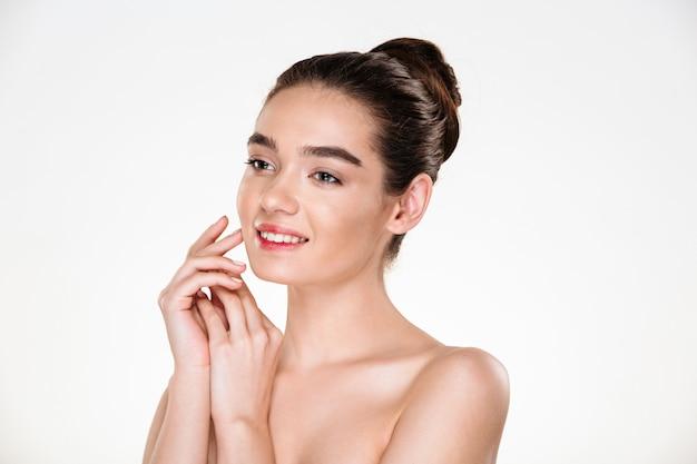 Imagem de mulher morena com cabelos em coque e maquiagem natural, sorrindo e olhando de lado Foto gratuita