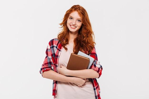 Imagem de mulher ruiva sorridente na camisa, abraçando livros Foto gratuita