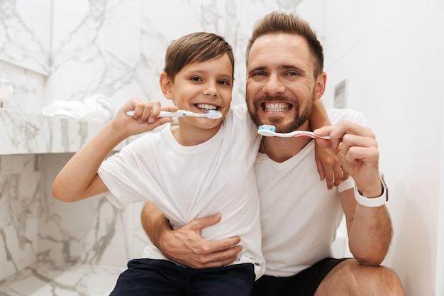 Imagem de pai e filho felizes sorrindo e limpando os dentes juntos no banheiro Foto Premium