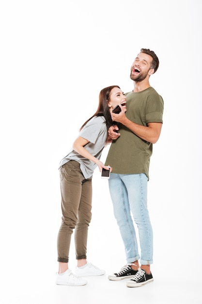 Imagem de rir a posição loving nova dos pares isolada. olhando de lado e segurando os telefones. Foto gratuita