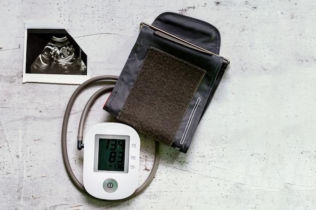 Imagem de ultrassonografia da 20ª semana de gestação e de um monitor de pressão arterial Foto Premium