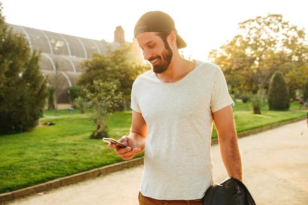 Imagem de um cara barbudo musculoso em um streetwear segurando e conversando no celular, enquanto caminha no parque verde Foto Premium