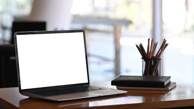 Imagem de um computador tablet com tela em branco, artigos de papelaria e cadernos na mesa de madeira. Foto Premium