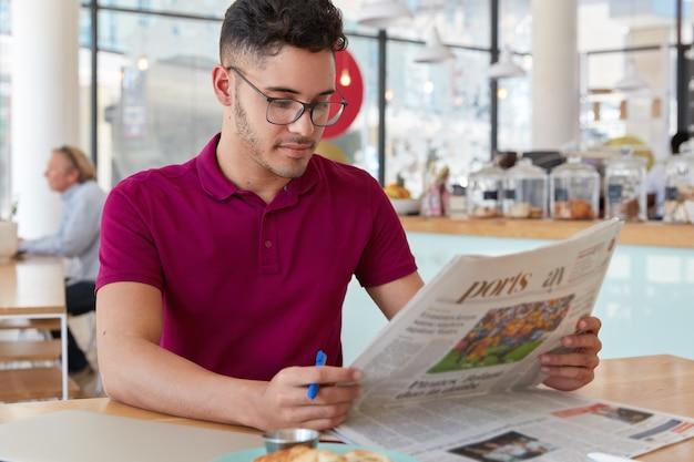 Imagem de um homem concentrado com expressão facial séria, lê jornal, descobre notícias do mundo, segura uma caneta para sublinhar os principais fatos, usa óculos e camiseta casual, posa sobre o interior do café Foto gratuita