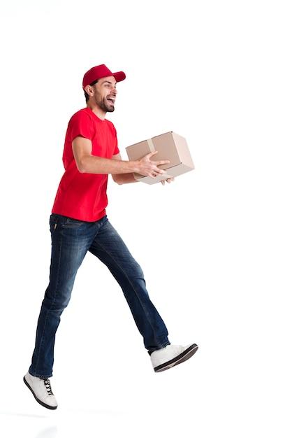 Imagem de um jovem entregador andando de lado com uma caixa Foto gratuita