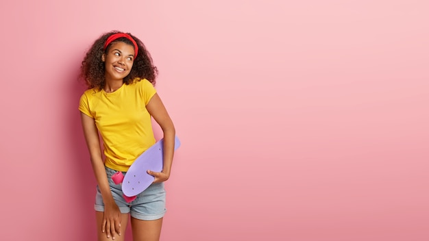 Imagem de uma adorável adolescente feliz com cabelo encaracolado posando em uma camiseta amarela Foto gratuita
