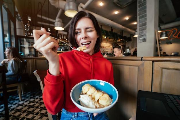 Imagem de uma jovem mulher sorridente e feliz se divertindo e tomando sorvete em uma cafeteria ou em um retrato de close up de restaurante Foto gratuita