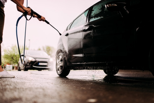 Imagem do baixo ângulo de uma pessoa que lava um carro com jato de alta pressão. Foto Premium