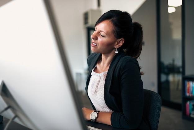 Imagem do close-up da mulher de negócios que tem o backpain. Foto Premium
