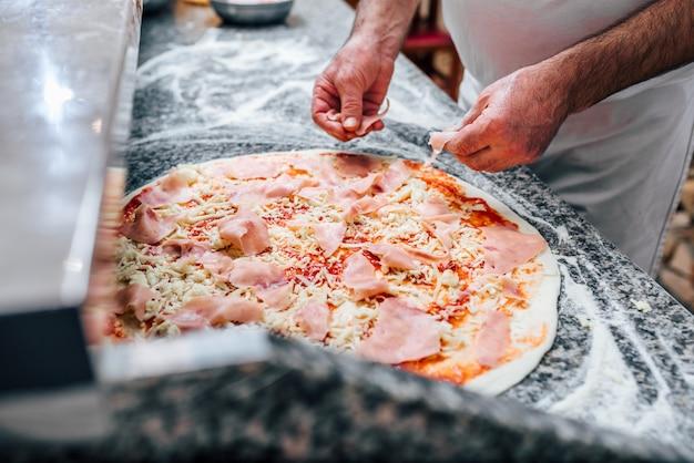 Imagem do close-up do cozinheiro chefe que faz a pizza. Foto Premium