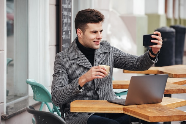 Imagem do homem morena alegre fazendo selfie ou skyping enquanto descansava no café de rua e tomando café de vidro Foto gratuita