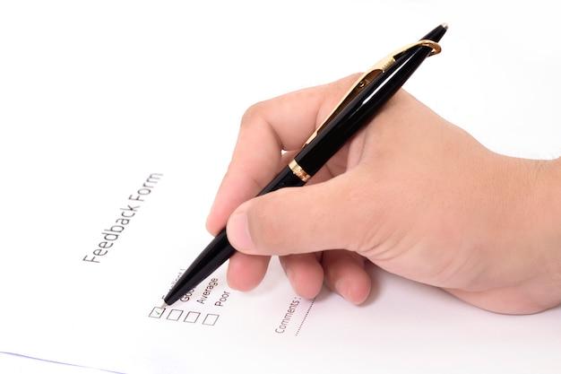 Imagem do homem que enche o formulário de feedback com a pena. Foto Premium