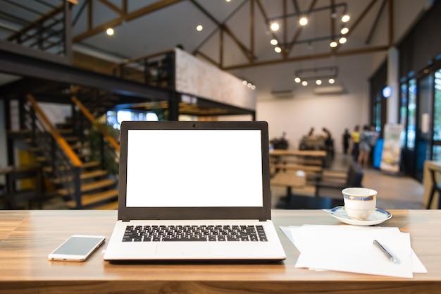 Imagem do modelo do portátil com a tela branca vazia na tabela de madeira na cafetaria. Foto Premium