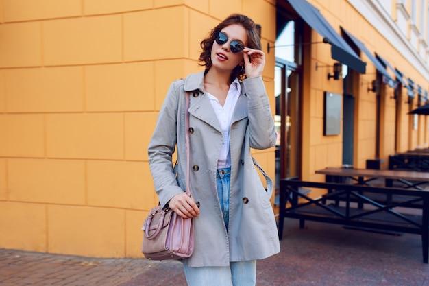 Imagem do outono da fêmea encantador à moda no revestimento bege que anda exterior. olhar de rua na moda. Foto gratuita