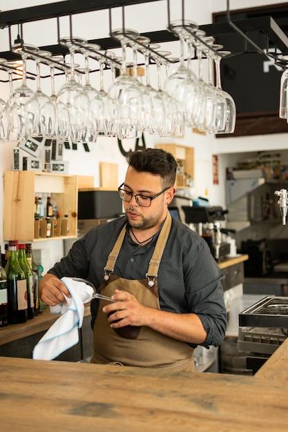 Imagem do vidro de vinho da limpeza do empregado de mesa em um bar. profissão, conceito de estilo de vida, trabalho. Foto Premium
