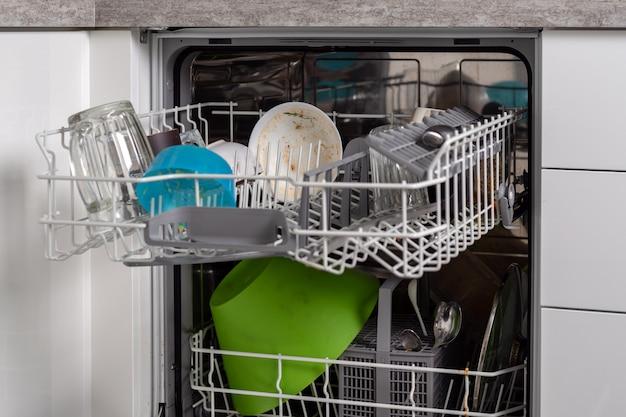 Imagem emoldurada de uma máquina de lavar louça com uma louça suja dobrada Foto Premium