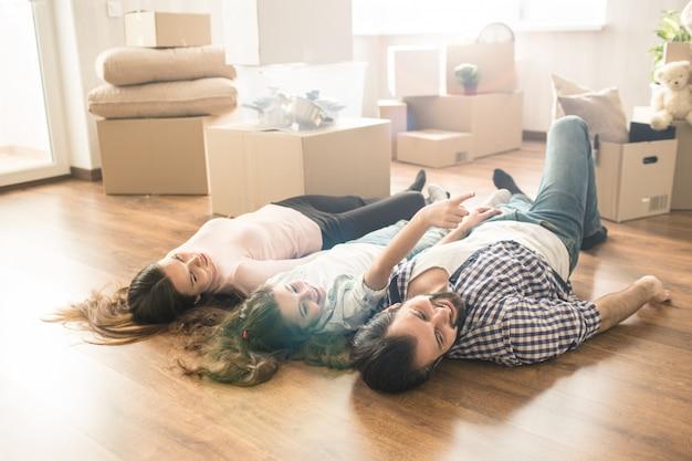 Imagem engraçada da família, deitado no chão em seu próprio apartamento novo. eles se divertem muito juntos. eles também estão procurando em algum lugar à direita. Foto Premium