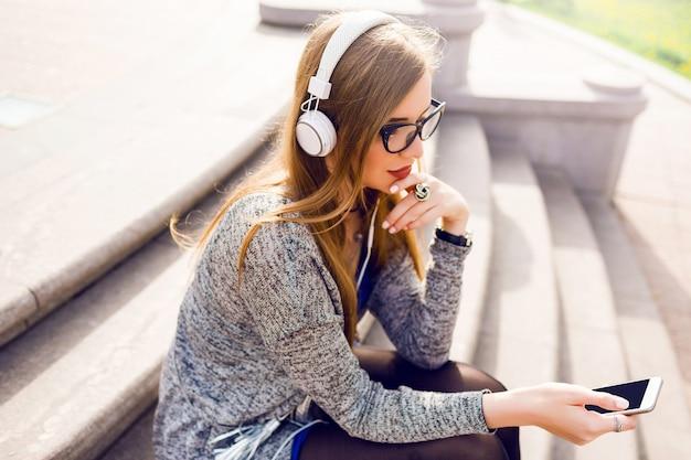 Imagem ensolarada de estilo de vida de verão da bela jovem loira ouvindo música por fones de ouvido, segurando o telefone móvel, sentado na rua, sonhando. vestindo roupa elegante primavera. Foto gratuita