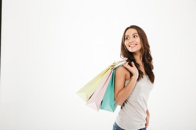 Imagem horizontal da moda mulher posando na câmera com pacotes de compras na mão, isolado sobre o espaço da cópia de parede branca Foto gratuita