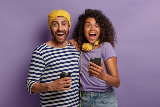 Imagem horizontal de um casal alegre e diverso passando um tempo juntos, assistindo a vídeos engraçados de redes sociais, abraçando e abrindo muito as bocas, animado com a incrível relevância, usando smartphone, bebendo café Foto gratuita
