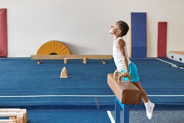 Imagem horizontal de um habilidoso garoto ginasta afro-americano se preparando para uma competição de ginástica artística Foto gratuita