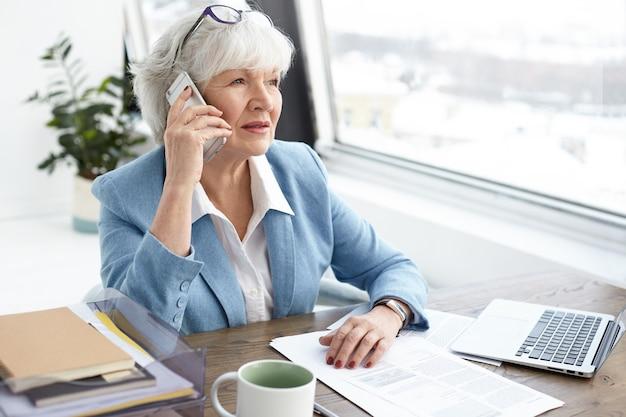 Imagem interna de uma banqueira madura de cabelos grisalhos de sessenta anos trabalhando em um escritório elegante, discutindo detalhes de um caso civil com seu cliente no telefone celular, sentado na mesa perto da janela, usando um laptop Foto gratuita