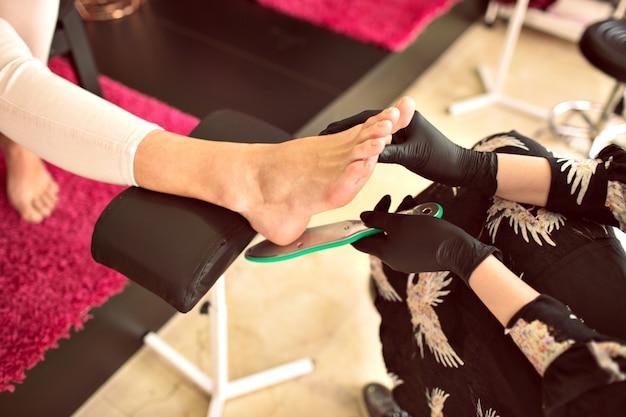 Imagem interna no salão de beleza, uma mulher fazendo pedicure para outra, trabalhadora na indústria da beleza, detalhes do serviço de unhas. cores tonificadas, ocupação manicure. Foto gratuita