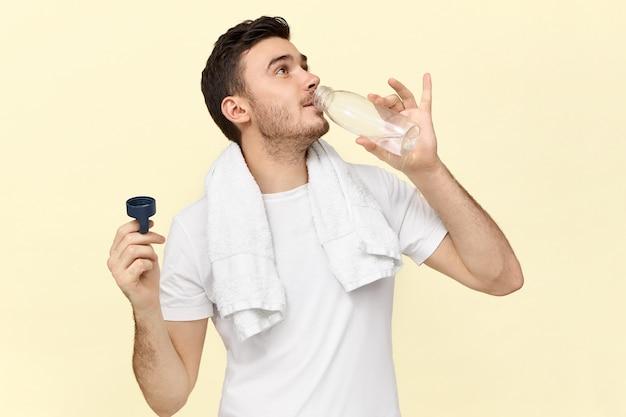 Imagem isolada de jovem bonito e confiante com uma toalha em volta do pescoço, segurando uma garrafa de plástico, se refrescando após o exercício físico na academia, bebendo água avidamente, vestindo uma camiseta branca Foto gratuita