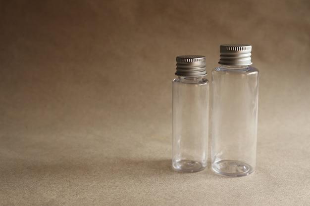 Imagem modelo de uma garrafa de vidro transparente com uma tampa de metal em um fundo marrom Foto Premium