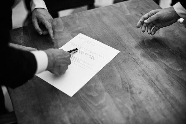 Imagem monocromática de noivo assinar documentos de registro de casamento. Foto Premium