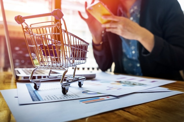 Imagem recortada da mulher que fornece informações sobre cartões e chave no telefone ou laptop enquanto faz compras on-line. Foto gratuita