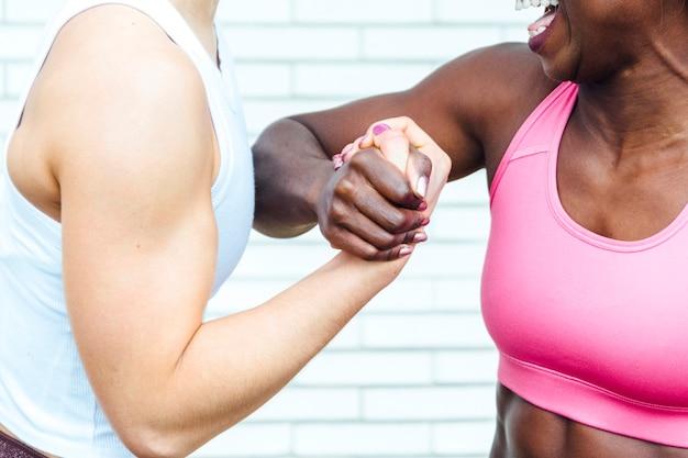 Imagem recortada de duas mulheres de mãos dadas. a mão à esquerda é de uma jovem branca. o da direita é de uma jovem negra. Foto Premium