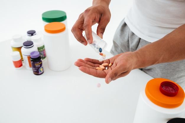 Imagem recortada de jovem desportista segurando vitaminas e comprimidos de esporte. Foto gratuita