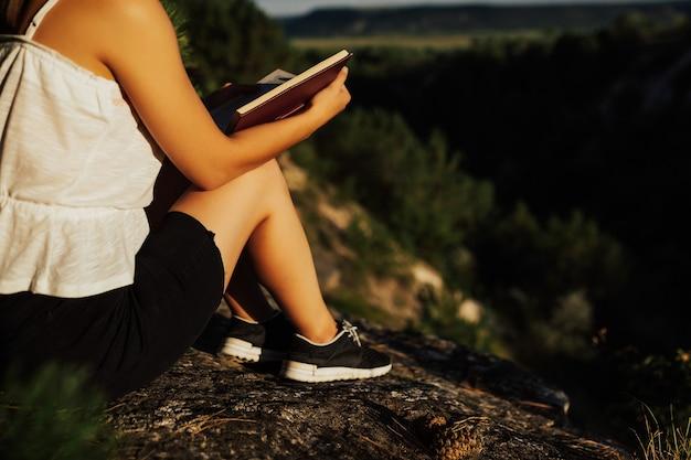 Imagem recortada de menina na rocha, lendo o livro. ela está lendo um livro em um dia ensolarado de verão. Foto Premium
