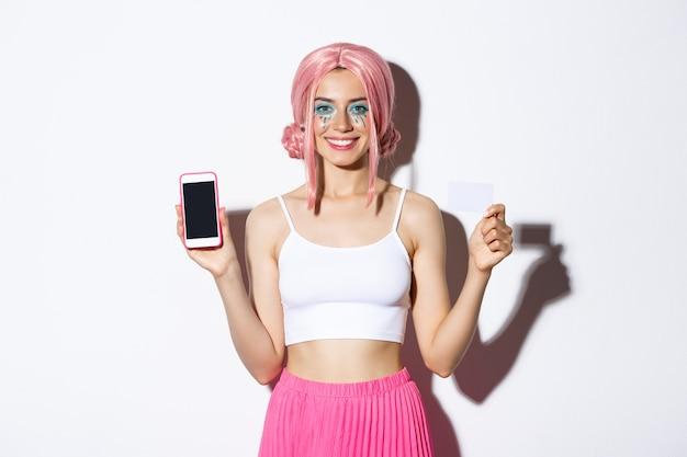 Imagem sorridente linda garota na peruca rosa, com maquiagem brilhante, mostrando o cartão de crédito e a tela do celular, em pé. Foto gratuita