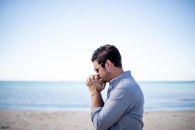 Imagem superficial de um homem perto da praia com as mãos perto da boca enquanto orava Foto gratuita