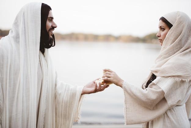 Imagem superficial de uma mulher vestindo um manto bíblico agarrando o pão das mãos de jesus cristo Foto gratuita