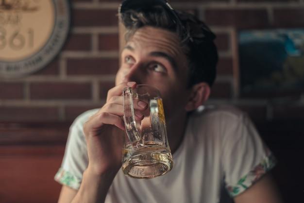 Imagem superficial de uma pessoa segurando um copo de cerveja vazio Foto gratuita