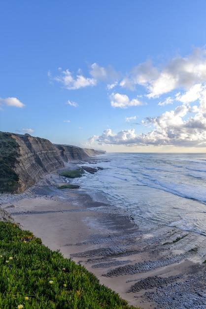 Imagem vertical da praia rodeada pelo mar e falésias ao sol e céu nublado Foto gratuita