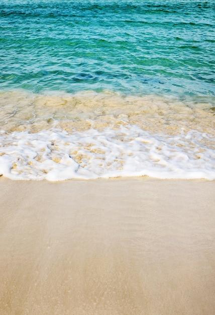 Imagem vertical da praia rodeada pelo mar sob o sol Foto gratuita