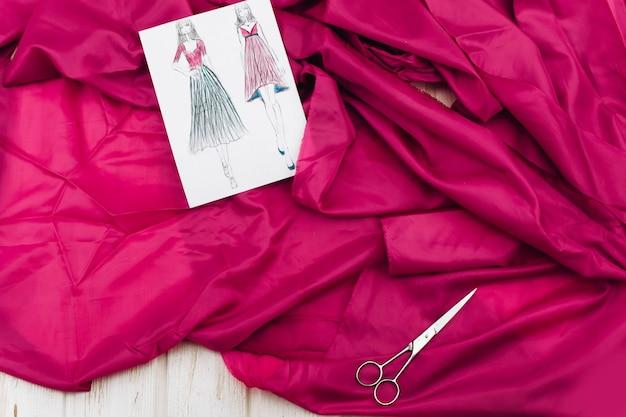 Imagens com modelos de vestido, pano rosa e outros acessórios para artesanato estão na mesa Foto Premium