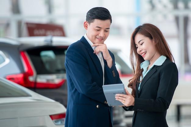 Imagens de clientes asiáticos e vendedores felizes que compram carros novos que celebram contratos de vendas com revendedores de automóveis. Foto Premium
