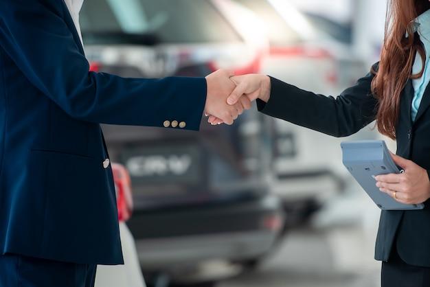Imagens de clientes e vendedores asiáticos, de mãos dadas, felizes em comprar carros novos que fazem acordos de vendas com revendedores de automóveis. Foto Premium