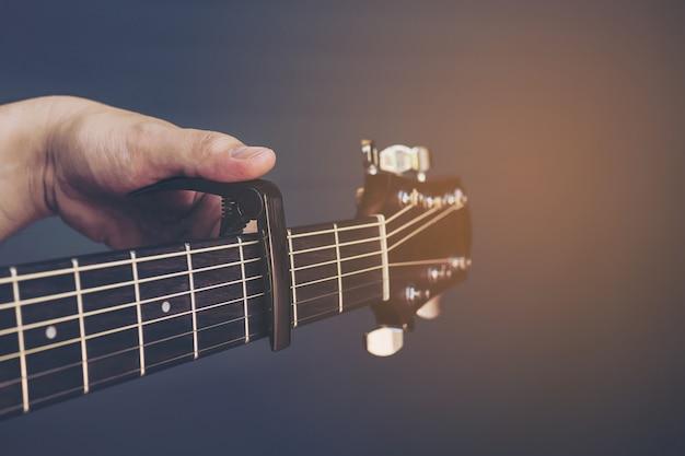 Imagens de cor vintage do homem colocando o capo de guitarra sobre fundo cinza Foto gratuita