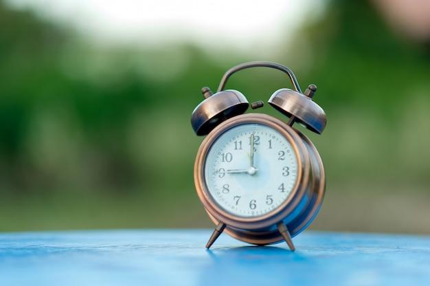 Imagens de despertador dourado colocado sobre uma mesa azul, fundo verde conceito pontual com espaço de cópia Foto Premium