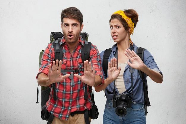 Imagens de elegantes jovens turistas masculinos e femininos europeus, viajantes ou aventuras parecendo frustrados e preocupados, mostrando o gesto de parada com as mãos, tentando resolver conflitos durante a viagem Foto gratuita