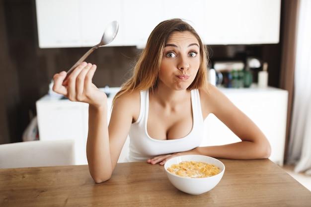 Imagens de garota jovem e atraente comendo flocos de milho com leite na cozinha e tirando sarro Foto gratuita