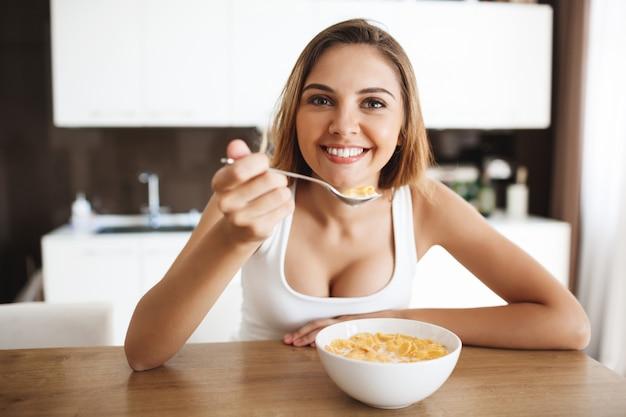 Imagens de garota jovem e atraente comendo flocos de milho com leite na cozinha sorrindo Foto gratuita