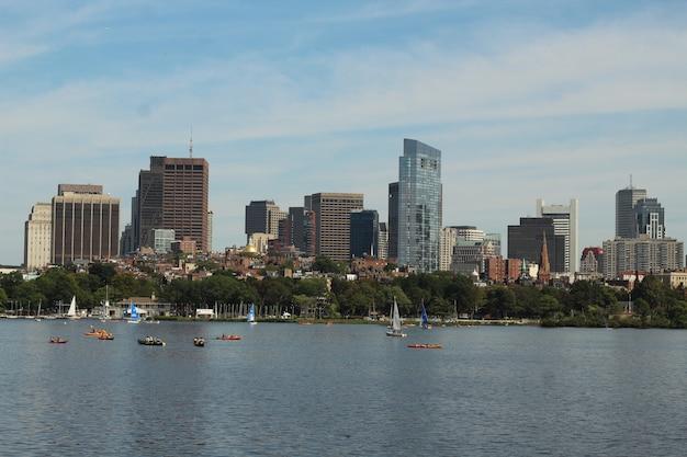 Imagens de horizonte de barcos navegando na água perto de uma grande cidade em um dia ensolarado Foto gratuita